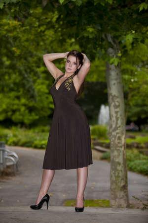 tetona: Un fresco buscando hermosa mujer Morena en su veintena de pie en un parque en frente de un árbol Foto de archivo