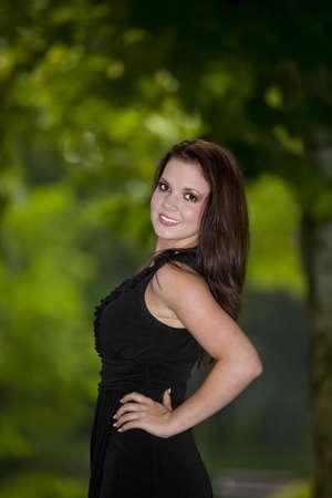 tetona: Un sonriente mujer hermosa morena de unos veinte años posando en un parque