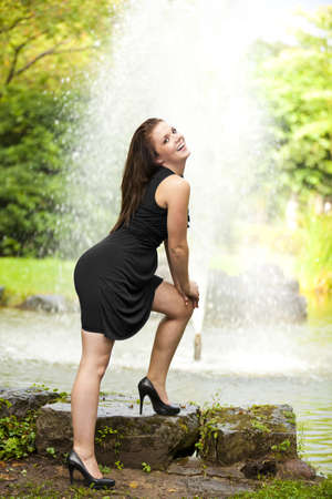 A smiling beautiful brunette woman in her twenties standing next to a pond with a fountain in the background Stock Photo - 10684595