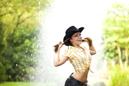 area sexy: A smiling beautiful brunette woman with a cowboy hat in her twenties tearing her hair, photographed in a park with a fountain in the background