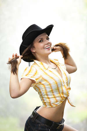 A smiling beautiful brunette woman with a cowboy hat in her twenties tearing her hair, photographed in a park with a fountain in the background photo