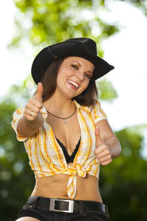 A laughing beautiful brunette woman with a cowboy hat in her twenties sitting in a park and posing with the thumbs up sign Stock Photo - 10684564