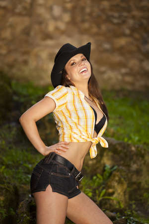 A laughing beautiful brunette woman with a cowboy hat in her twenties posing in a park photo