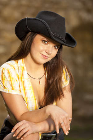 a smiling beautiful brunette woman with a cowboy hat in her twenties posing in a park photo
