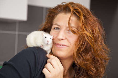 A beautiful smiling woman in her thirties with a rat sitting on her shoulder at a veterinarian