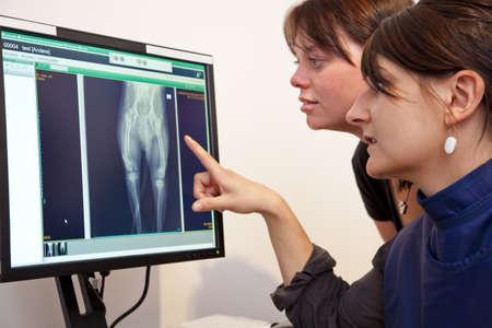 veterinaria: Un veterinario explicando una imagen de rayos X para el due�o del animal dom�stico femenino
