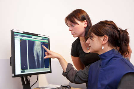 A veterinarian explaining a x-ray picture to the female pet owner photo