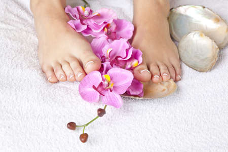A beauty concept - feet with acrylic toenails, flowers, shells and crystals photo