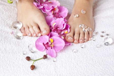 pedicura: Un concepto de belleza - pies con las uñas acrílicas, las flores y cristales