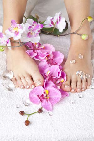 A beauty concept - feet with acrylic toenails, flowers and crystals photo