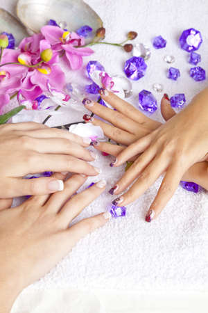 human fingernail: A beauty concept - hands with acrylic fingernails, flowers, shells and crystals Stock Photo