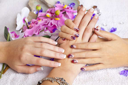A beauty concept - hands with acrylic fingernails, flowers, shells and crystals photo