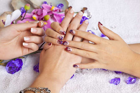 A beauty concept - hands with acrylic fingernails, flowers, shells and crystals Stock fotó