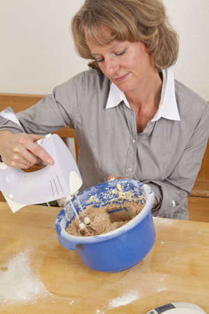 stirring: A smiling mature woman in her forties mixing dough with an electric hand mixer