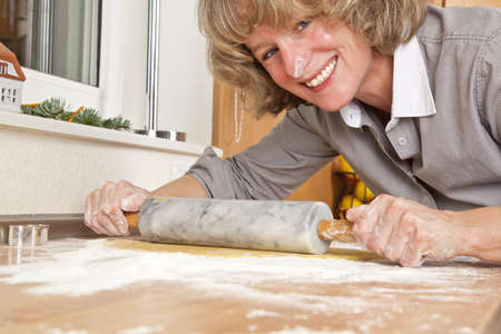A smiling woman in her forties rolling dough on a kitchen table with a rolling pin photo