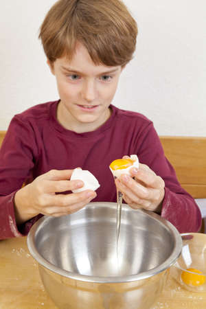 An eleven years old boy sitting in the kitchen in front of a bowl and separating egg white from egg yolk photo
