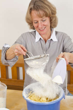 A smiling woman in her forties mixing dough with an electric hand mixer and sieving flour into the bowl