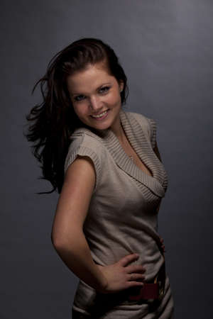 A low key studio shot of a smiling brunette and beautiful young woman, photographed on a grey and grainy paper background photo