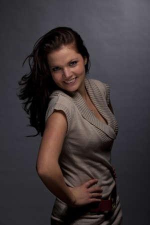 tetona: Un estudio de baja clave de tiro de una mujer joven y sonriente morena y hermosa, fotografiado sobre un fondo de papel gris y granulosa