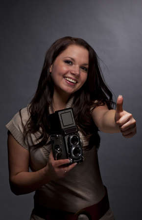 A low key studio shot of a smiling brunette and beautiful young woman holding a medium format camera and posing with the thumbs up sign, photographed on a grey and grainy paper background photo