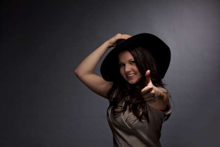A low key studio shot of a smiling brunette and beautiful young woman wearing a hat and posing with the thumbs up sign, photographed on a grey and grainy paper background photo