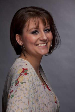 brown eyes: Un estudio discreto tiro de una mujer joven y sonriente morena y hermosa, fotografiado sobre un fondo de papel gris y granulosa