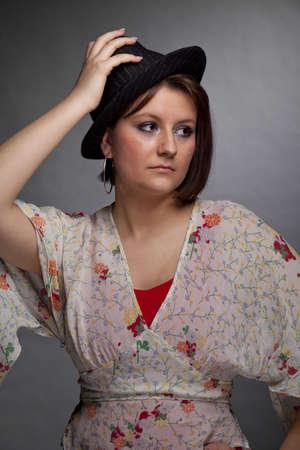 heartsick: Un tiro bajo estudio clave de una triste mujer que busca joven morena y hermosa con un sombrero, fotografiado en una gris y fondo de papel granulado