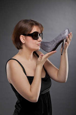 A low key studio shot of a brunette and beautiful young woman with sunglasses kissing a shoe, photographed on a grey and grainy paper background photo