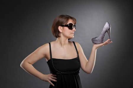 A low key studio shot of a brunette and beautiful young woman with sunglasses holding a shoe, photographed on a grey and grainy paper background photo