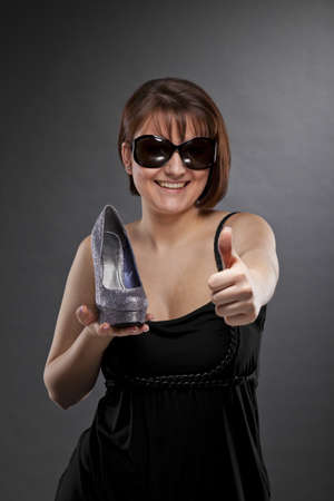 A low key studio shot of a smiling brunette and beautiful young woman with sunglasses holding a shoe and posing with the thumbs up sign, photographed on a grey and grainy paper background Stock Photo - 13442234