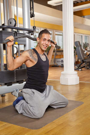 latissimus: A smiling young man in his twenties exercising in a fitness studio and training his latissimus and looking into camera