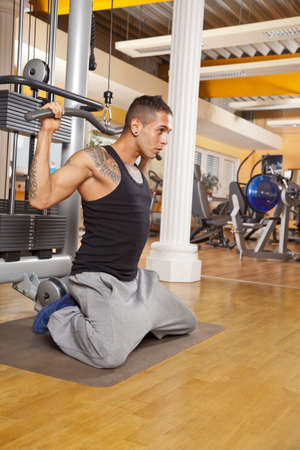 A young man in his twenties exercising in a fitness studio and training his latissimus photo