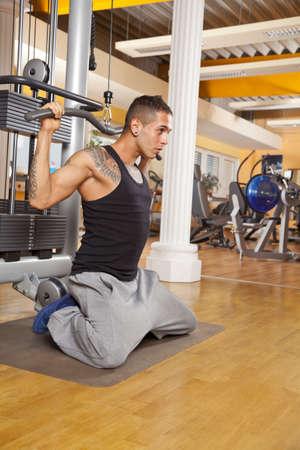latissimus: Un giovane poco pi� che ventenne che esercitano in una sala fitness e addestrando i suoi latissimus