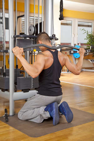 A back view of a young man in his twenties exercising in a fitness studio and training his latissimus photo