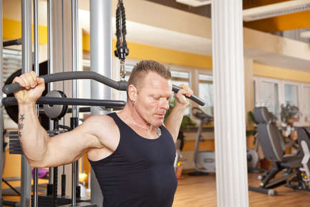 dorsi: A man in his forties exercising in a fitness studio and training his latissimus