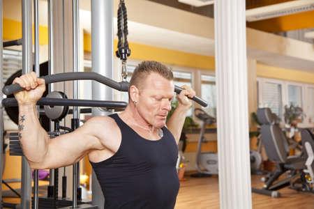 latissimus: Un uomo sulla quarantina che esercitano in una sala fitness e addestrando i suoi latissimus Archivio Fotografico