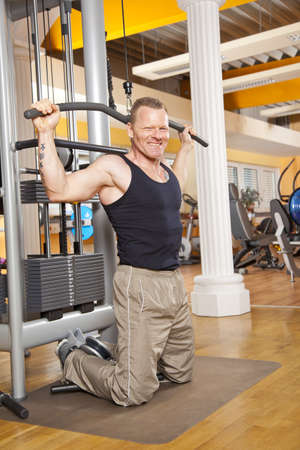 latissimus: A smiling man in his forties exercising in a fitness studio training his latissimus and looking into camera