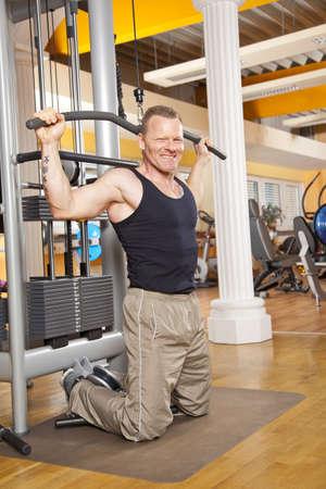 latissimus: Un uomo sorridente quarantenne esercitare un corso di formazione in palestra i suoi dorsali e guardando la telecamera