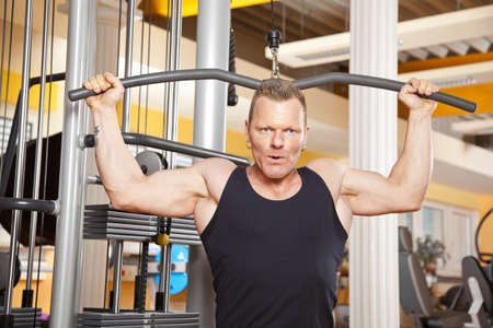 latissimus: A handsome man in his forties exercising in a fitness studio training his latissimus and looking into camera