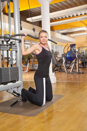 latissimus: A smiling beautiful young woman in her twenties exercising in a fitness studio training her latissimus and looking into camera