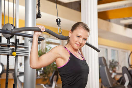 A smiling beautiful young woman in her twenties exercising in a fitness studio training her latissimus and looking into camera photo