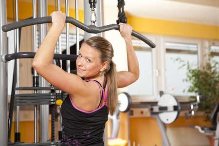 latissimus: Una donna sorridente giovane e bella in vent'anni esercitare in un corso di formazione fitness sue dorsali e guardando la telecamera