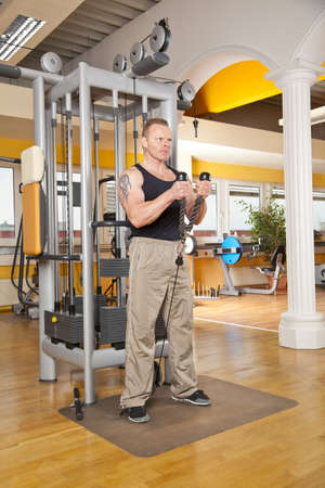 male age 40's: A handsome man in his forties exercising in a fitness studio training his biceps