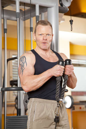 mid adult man: A handsome man in his forties exercising in a fitness studio training his biceps and looking into camera Stock Photo