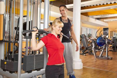 latissimus: Un sorridente bella giovane donna sulla ventina che esercitano in un centro fitness formazione sue dorsale e di essere istruito dal suo personal trainer