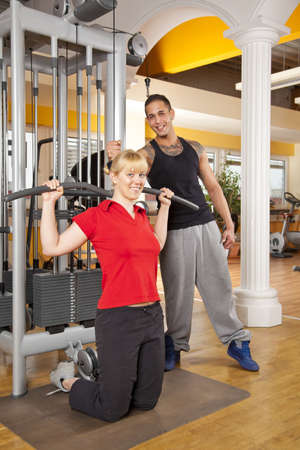 A smiling beautiful young woman in her twenties exercising in a fitness studio training her latissimus and being instructed by her personal trainer, both looking into camera photo