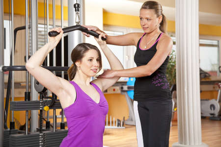 A smiling beautiful young woman in her twenties exercising in a fitness studio training her latissimus and being instructed by her personal female trainer