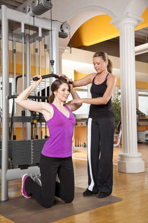 A smiling beautiful young woman in her twenties exercising in a fitness studio training her latissimus and being instructed by her personal female trainer photo
