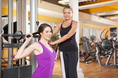 latissimus: A smiling beautiful young woman in her twenties exercising in a fitness studio training her latissimus and being instructed by her personal female trainer, both looking at camera Stock Photo