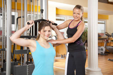 A smiling beautiful teenage woman  exercising in a fitness studio training her latissimus and being instructed by her personal female trainer, both looking at camera Stock Photo - 14189679